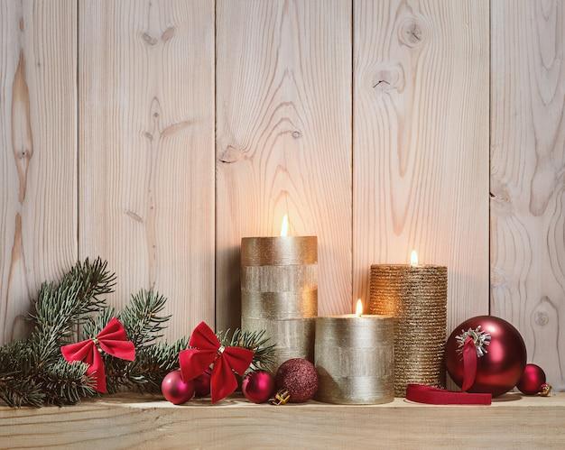 クリスマスキャンドルの光。モミの枝とお祭りのボール。