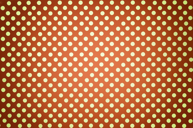 Light orange background from wrapping paper with a pattern of golden polka dot closeup.