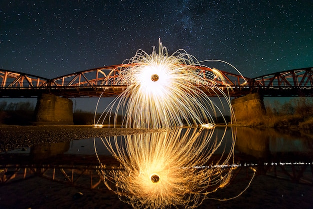 Light painting art concept. spinning steel wool in abstract circle, firework showers of bright yellow glowing sparkles on long bridge reflected in river water on blue night starry sky