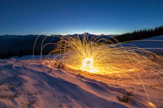 Light painting art. spinning steel wool in abstract circle, firework showers of bright yellow glowing sparkles on winter snowy valley on mountain ridge and blue night starry sky  .