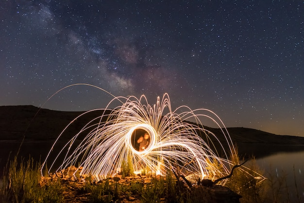 Light painting with sparks with the milky way in the sky