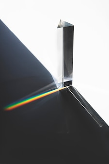 Light passing through a triangular prism with dark shadow on white surface