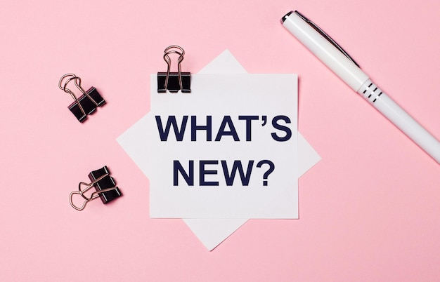 On a light pink background, black paper clips, a white pen and white note paper with the text what is new. flat lay