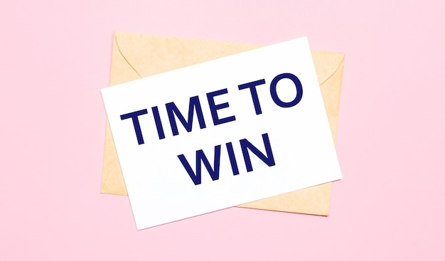 On a light pink background - a craft envelope. it has a white sheet of paper that says time to win.