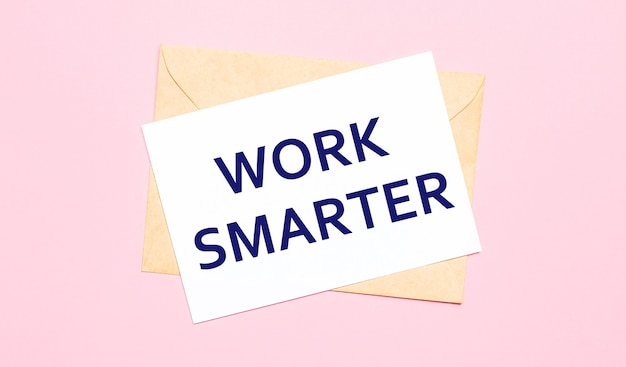 On a light pink background - a craft envelope. it has a white sheet of paper that says work smarter.