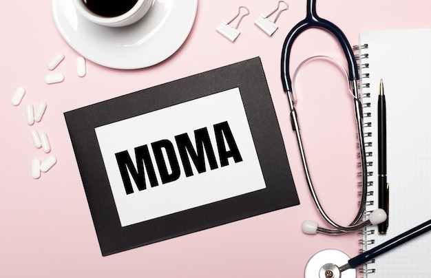 On a light pink background, a notebook with a pen, stethoscope, white pills, paper clips and a sheet of paper with the text mdma