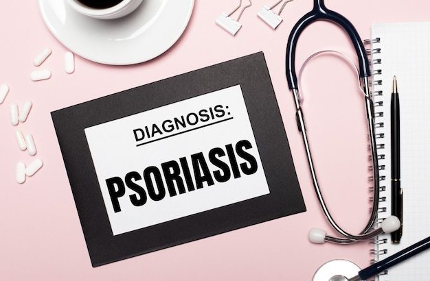On a light pink background, a notebook with a pen, stethoscope, white pills, paper clips and a sheet of paper with the text psoriasis. medical concept