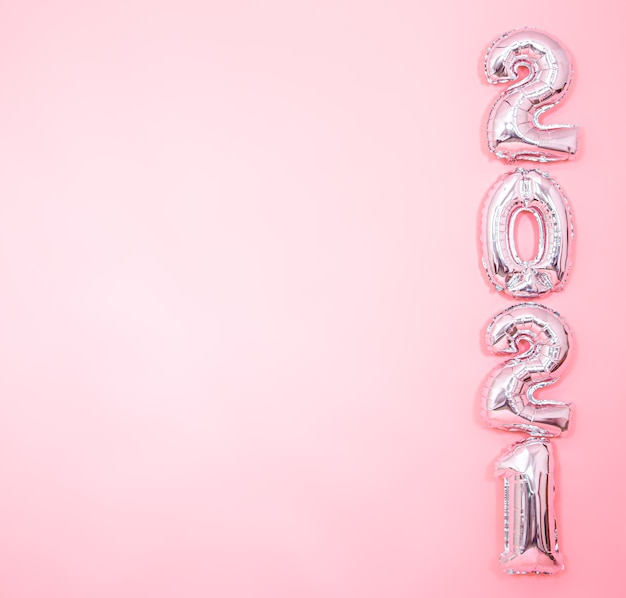 Light pink background with silver new years balloons in form of numbers on the right side, new year concept
