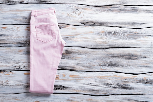 라이트 핑크 캐주얼 팬츠. 나무 배경에 여자의 바지입니다. 옷가게에서 시즌 세일. 심플한 디자인과 밝은 색상.