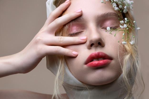 淡いピンクのアイシェード。白い花でポーズをとっている間、淡いピンクのアイシェードが目を閉じている美しいモデル