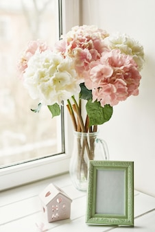 Light pink hydrangea flowers in glass vase, photo frame and tiny wooden house