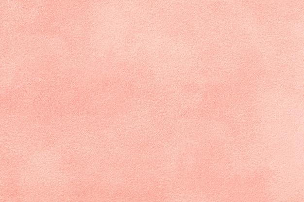 Светло-розовый матовый фон из замшевой ткани, крупным планом. бархатная текстура розовой фетровой ткани, макрос.