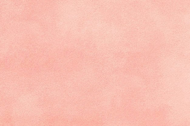 Light pink matte background of suede fabric, closeup. velvet texture of  rose felt textile, macro.