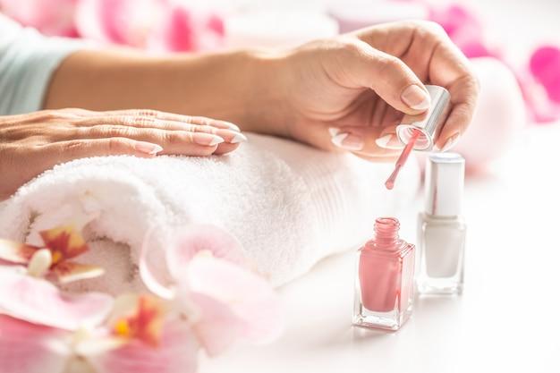 Светло-розовый лак для ногтей нанесен на руку женщины.