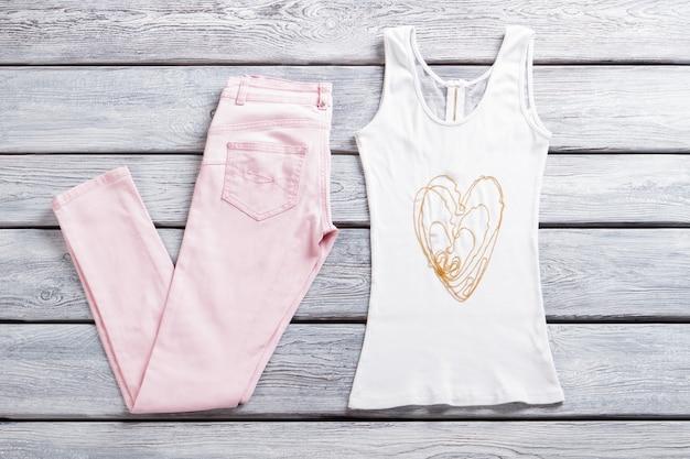 밝은 분홍색 바지와 상의. 지퍼가 달린 흰색 탱크탑. 작은 구슬 목걸이. 소녀의 여름옷과 장식품.