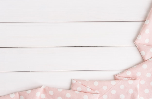 Light pink polka dots folded tablecloth over bleached wooden table. top view image. copyspace