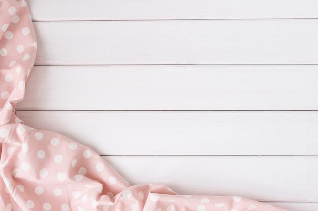 Светло-розовая скатерть в горошек на выбеленном деревянном столе. изображение вида сверху. copyspace