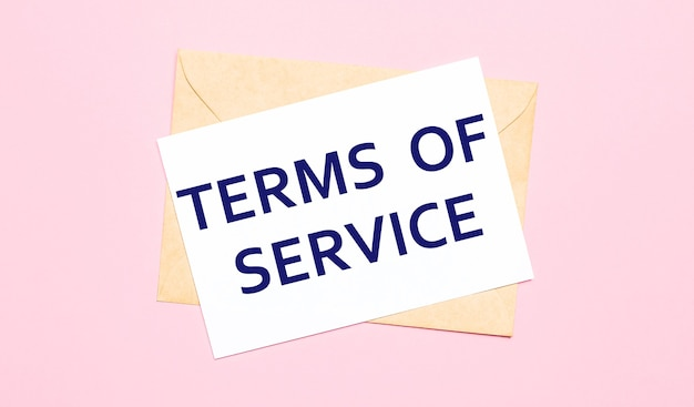 On a light pink surface  a craft envelope. it has a white sheet of paper that says terms of service