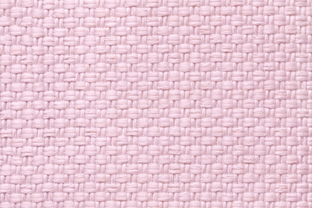 Light pink textile background with checkered pattern, closeup. structure of the fabric macro.