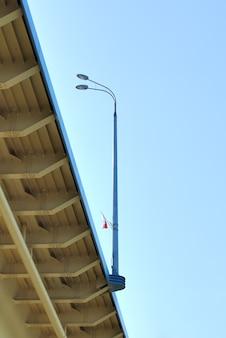 Light poles bridge span on the background of blue sky