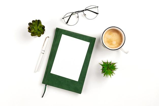コーヒーノートブックペングラスを備えた白い職場でのデザインプレゼンテーション用の軽いポストカードモックアップ...