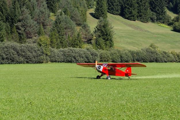 Светло-красный самолет, приземляющийся на зеленый луг, транспорт, на открытом воздухе