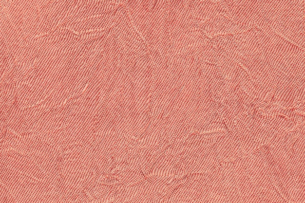 Light red wavy background from a textile material. fabric with fold texture closeup.