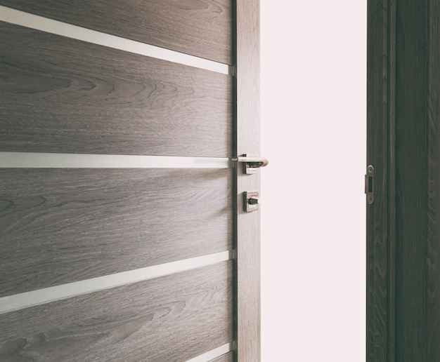 The light revealing through the half open wooden door in the house