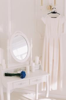 거울이 달린 옷걸이, 꽃다발 및 드레스 테이블에 웨딩 드레스가있는 가벼운 낭만적 인 인테리어