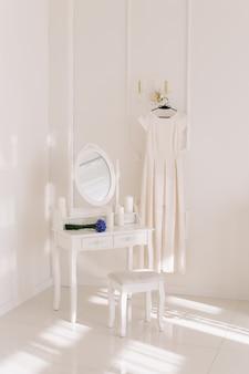 옷걸이에 웨딩 드레스, 신부 부케 및 거울이 달린 화장대가있는 가벼운 낭만적 인 인테리어