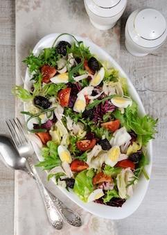 Легкий салат из микса листьев салата с помидорами, яйцом, кусочками куриной грудки и вялеными оливками