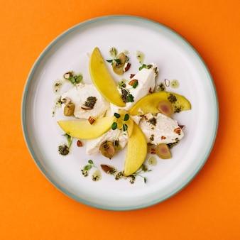 新鮮な桃、モッツァレラチーズ、グリーンサラダの軽いサラダが桃色の背景にミックスされています。上面図
