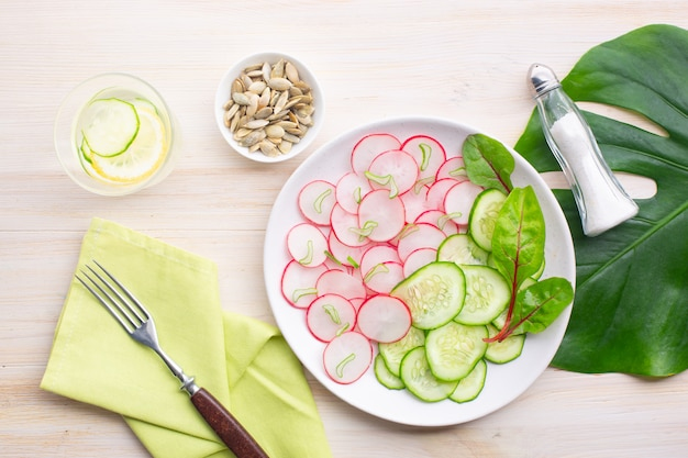 Light salad of radish with cucumber and detox water with cucumbers and lemon on the background of a large leaf of monstera.