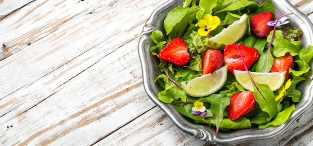 Light salad with greens, strawberries and lime.summer food