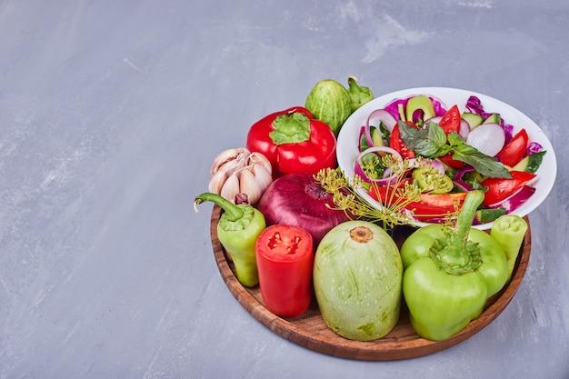 木製の大皿に野菜とハーブを添えた軽いサラダ。