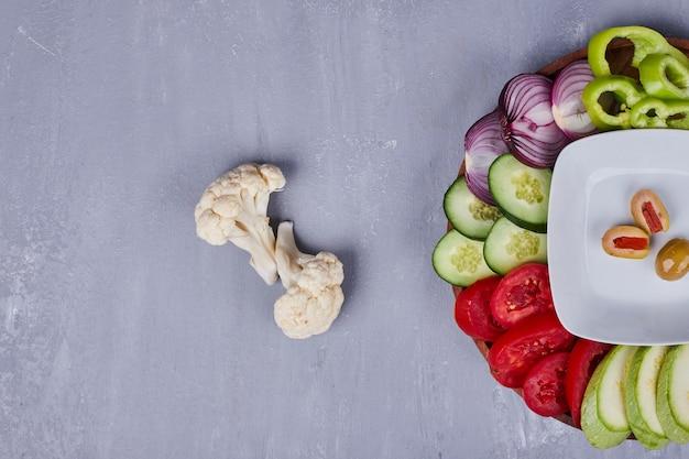 木製の大皿に野菜とハーブの軽いサラダ、上面図。