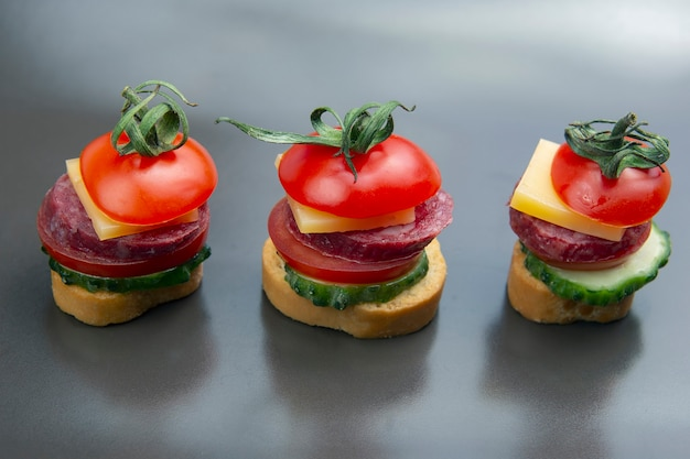 Light sandwiches made of vegetables, cheese and sausages. fast food and breakfast