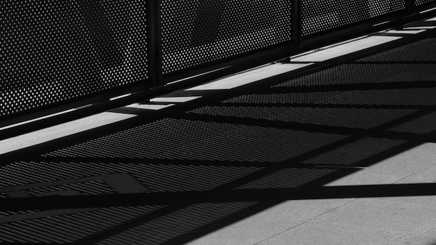 Light and shadow of wire mesh on pavement - monochrome