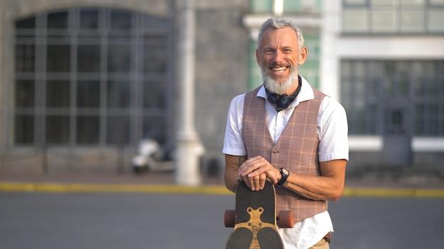 Light-skinned attractive bearded man having fun holding a longboard