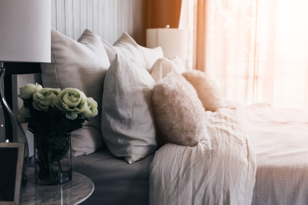 Light soft pillow on beautiful bed cozy bedroom with sun light from window interior concep