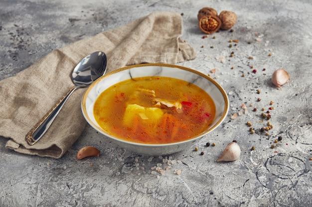 밝은 배경에 국수와 향신료가 들어간 닭고기 국물에 가벼운 수프