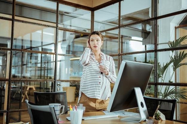 Светлый просторный офис. молодая беременная привлекательная темноволосая женщина, работающая в светлом просторном офисе