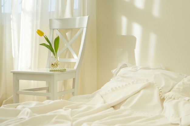 Premium Photo Light Spring Bedroom Interior Bed White Chair Glass With Yellow Tulip