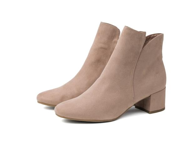 白い表面に分離された軽いスエードの女性の靴