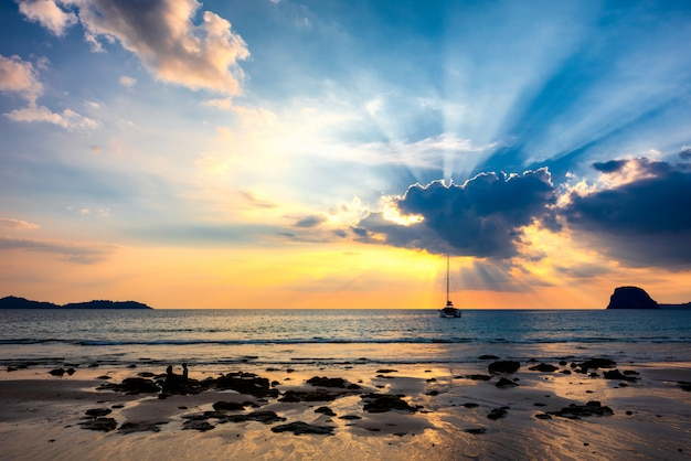 Light of sun pass through clouds with yacht in sea