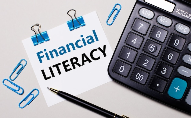 On a light surface, a calculator, a pen, blue paper clips and a sheet of paper with the text financial literacy. view from above.