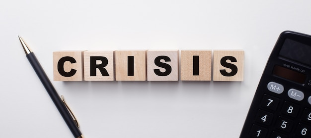 On a light surface between the calculator and the pen there are wooden cubes with the word crisis. financial concept