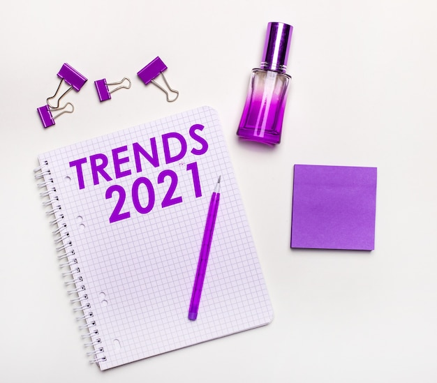 On a light surface - a lilac gift, perfume, lilac business accessories and a notebook with a lilac inscription trends 2021. flat lay. women's business concept