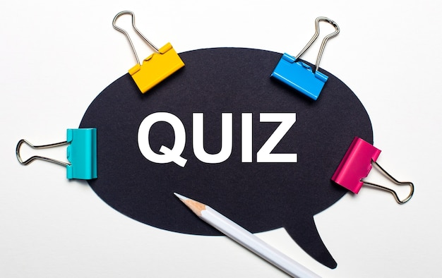 On a light surface, multi-colored paper clips, a white pencil and black paper with the words quiz