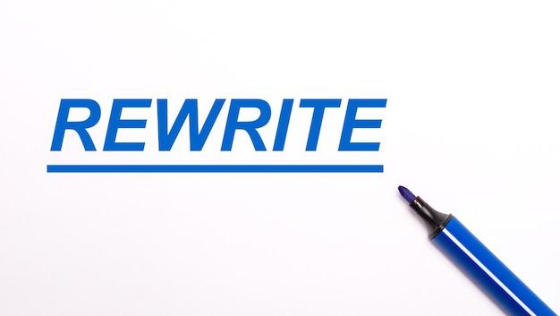 On a light surface, an open blue felt-tip pen and the text rewrite